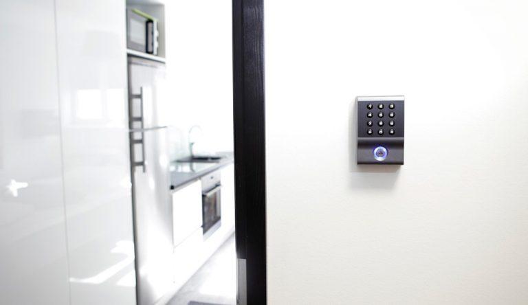 Huoneeseen auki oleva oviaukko ja oven vieressä Optima Access Control-kulunvalvontajärjestelmä koodinäppäimistö.
